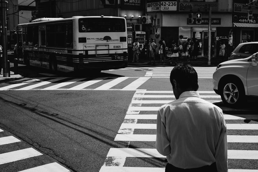 Man waits at a crosswalk in Tokyo, Japan