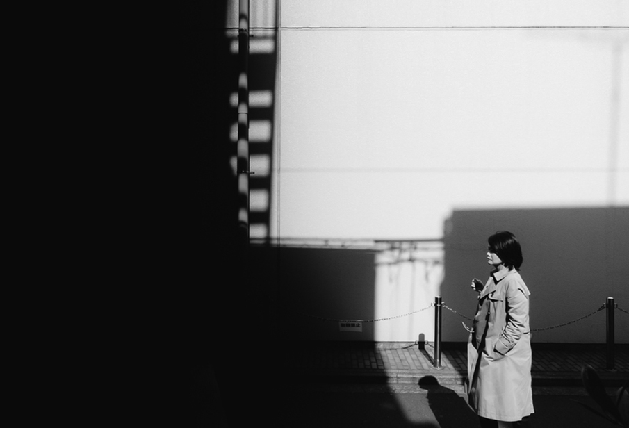 woman in trench coat walking down street