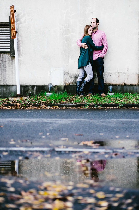 couple against a wall with water puddle