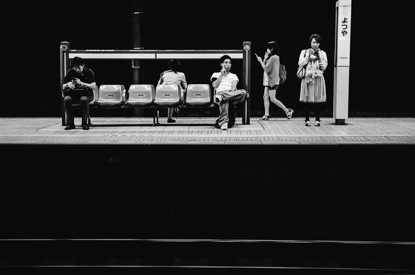 people user their phones while waiting on a train platform in Japan