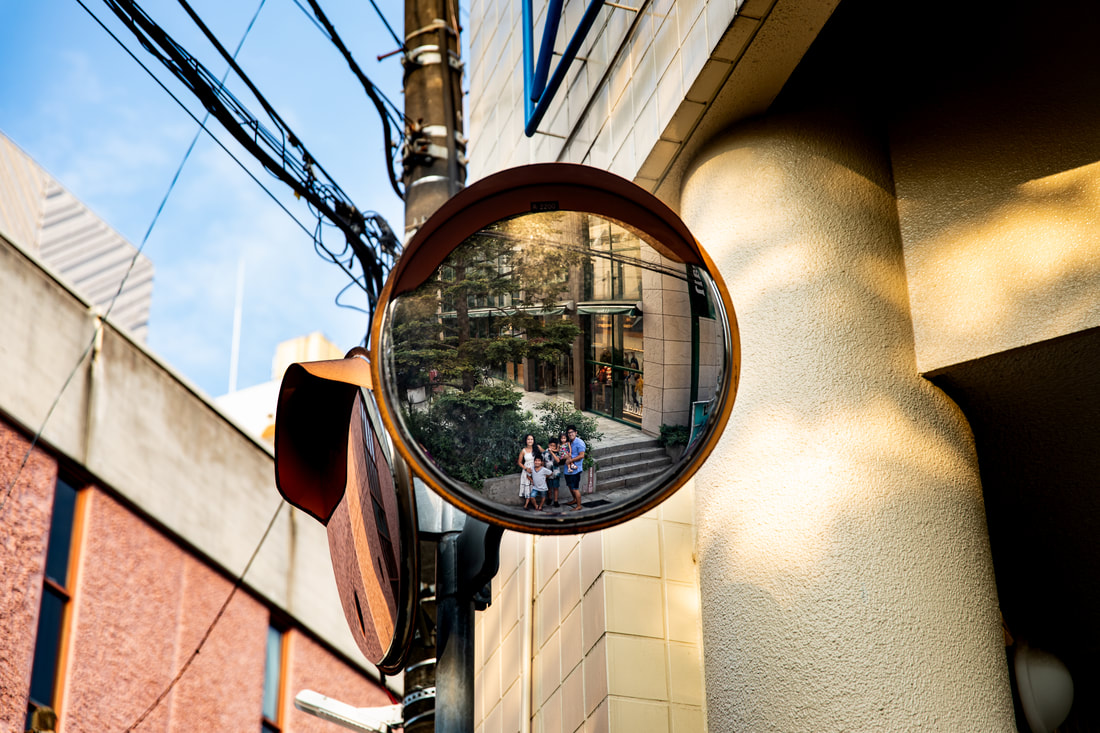 Family reflected in street mirror