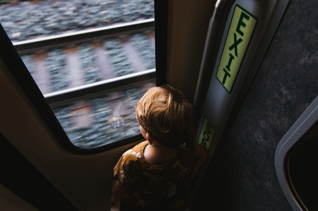 son looking outside of train