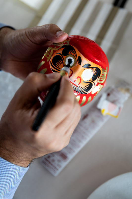 painting eye on Daruma Doll
