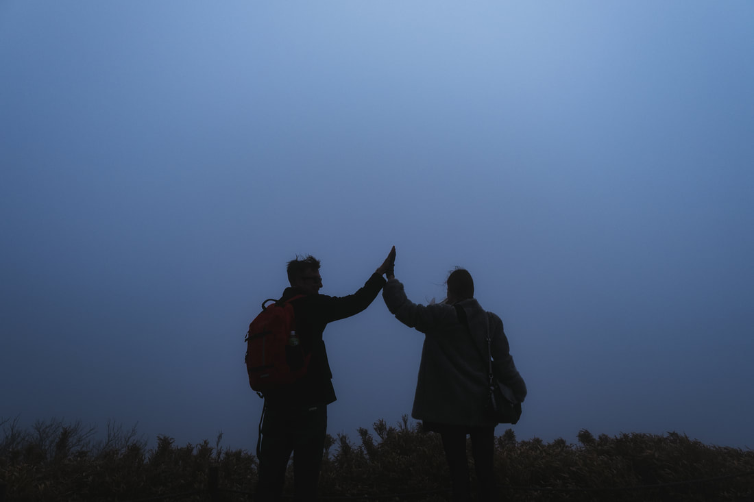 Friends high-five in fog