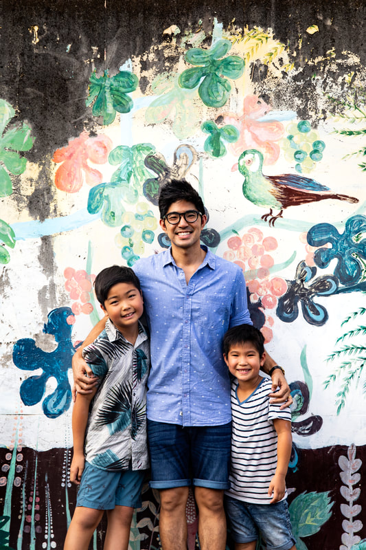 father and sons in front of mural
